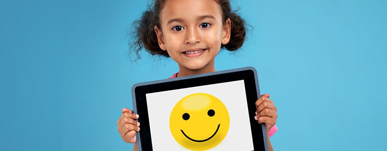 little girl holding a tablet with a smiling face on it
