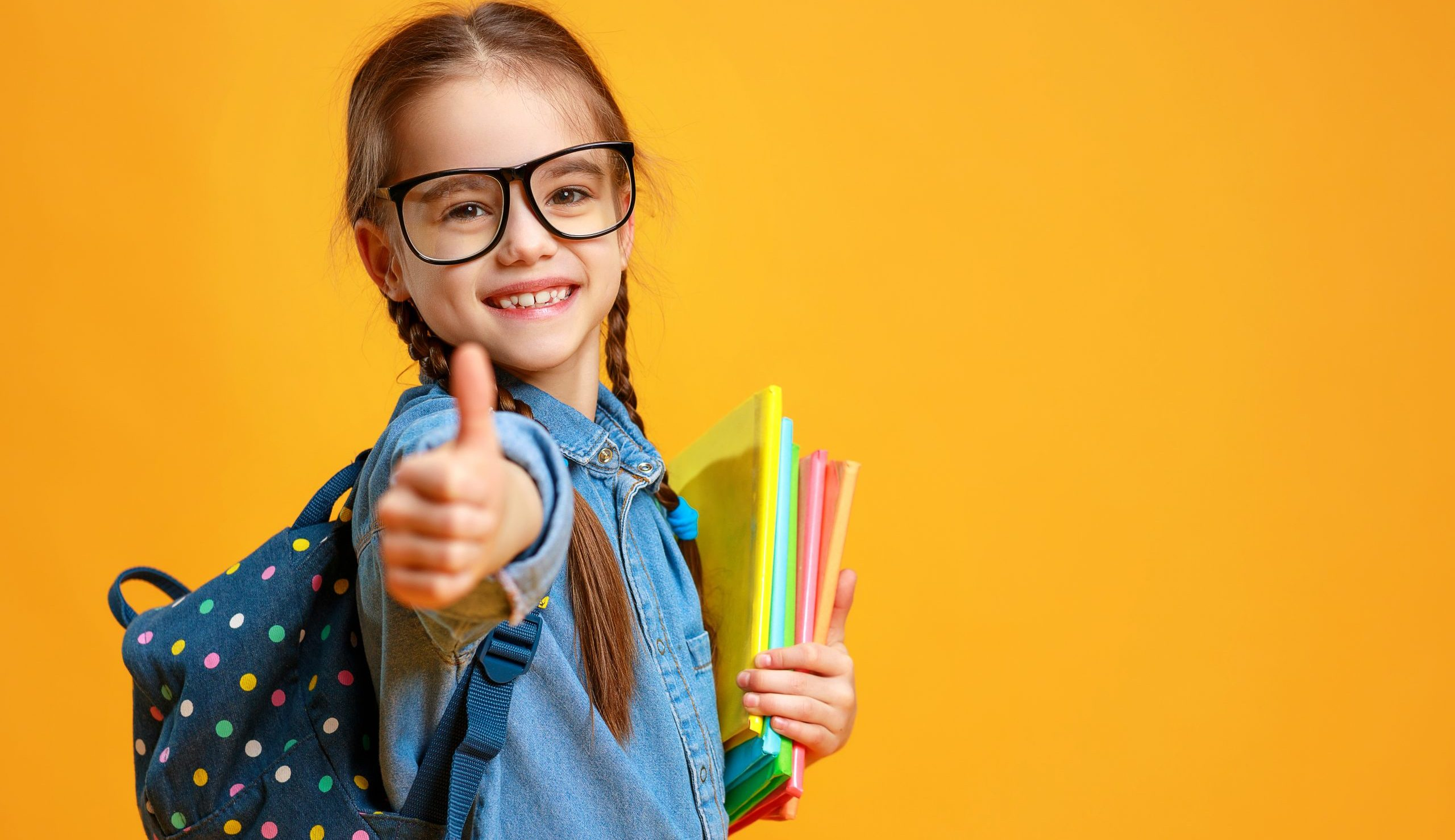 Child giving thumbs up with packback on ready to go back to school